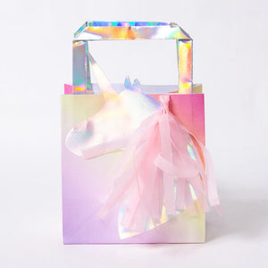 A party bag covered in iridescent foil with a unicorn-shaped badge on front