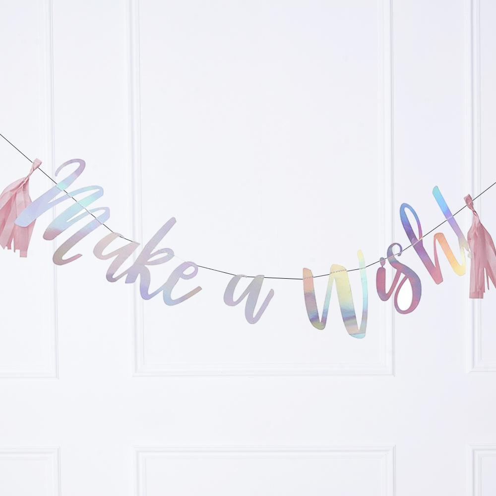 "An iridescent party banner with a message saying ""Make a Wish"" written in cursive text"