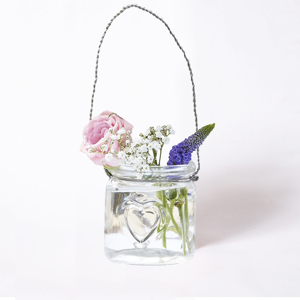 A glass hanging tealight filled with colourful flowers