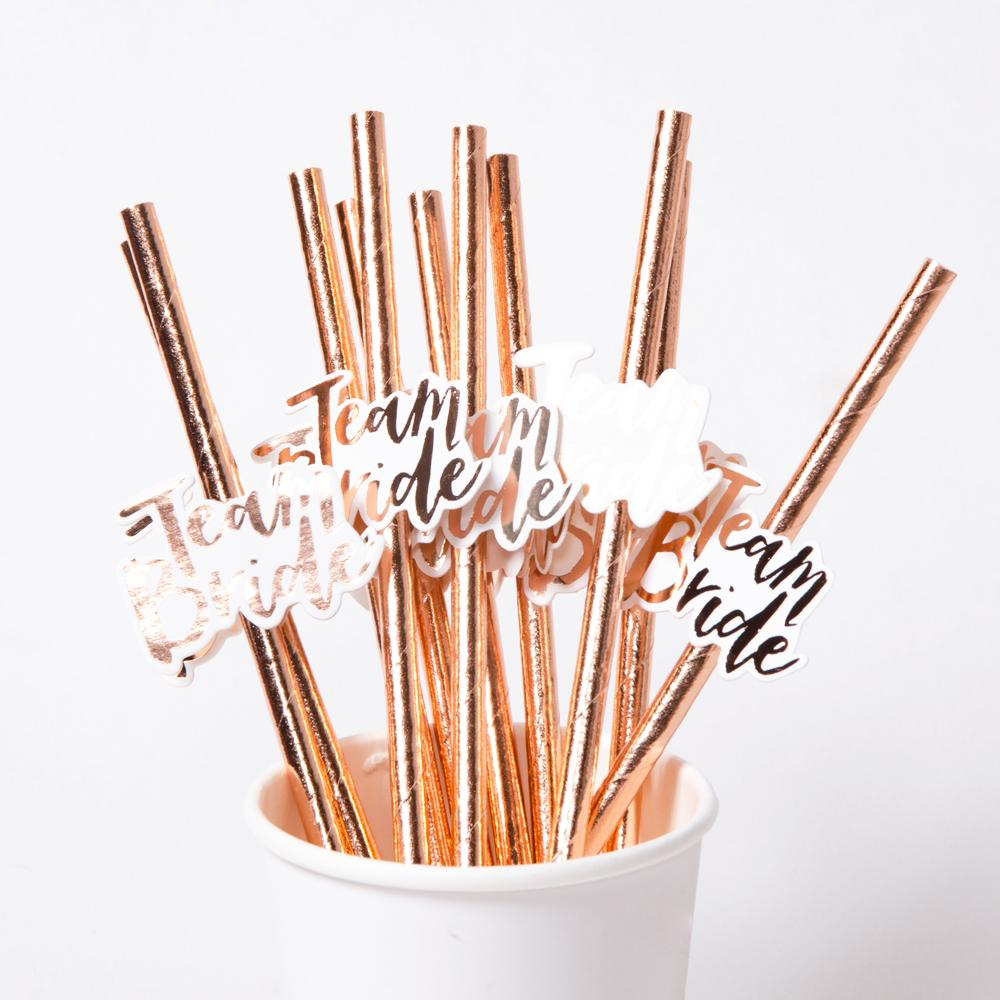 A cup filled with rose gold party straws for a hen party
