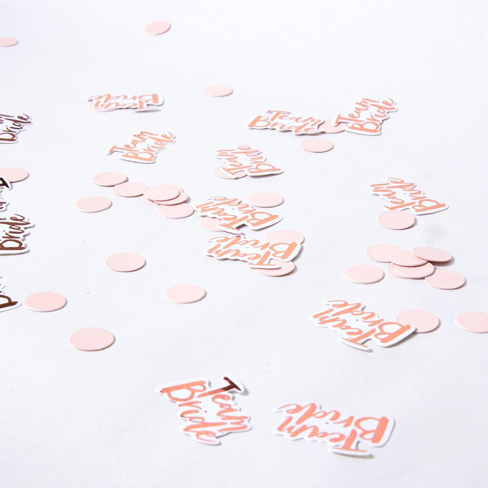 "A table with ""Team Bride"" hen party confetti scattered across it"