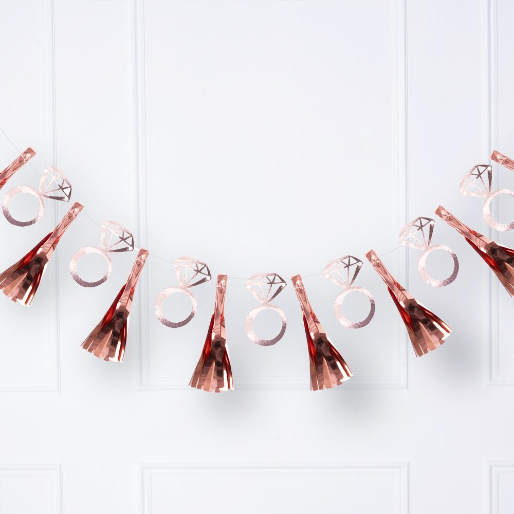 A hanging hen do party garland with rose gold foil tassels and engagement ring shapes