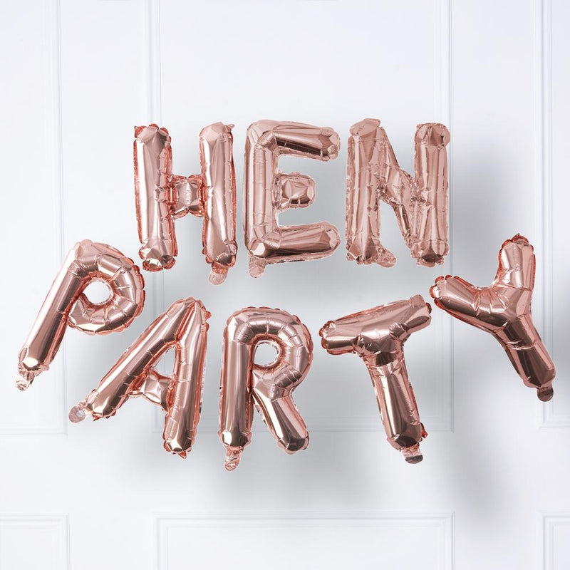 A shiny rose gold foil hen party balloon banner saying