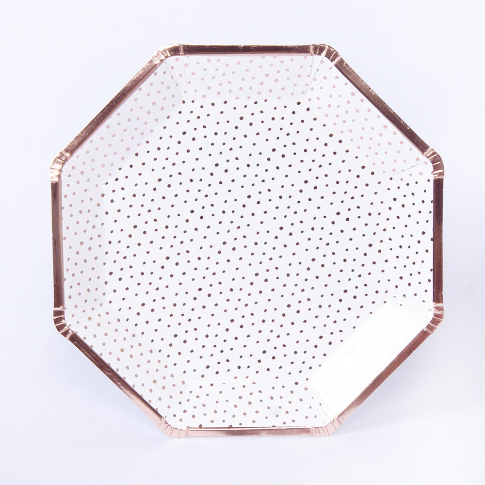 An octagonal paper party plate with a gold foil trim and dotty polka dot design