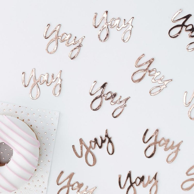 "Rose gold foil ""Yay"" confetti scattered across a party table"