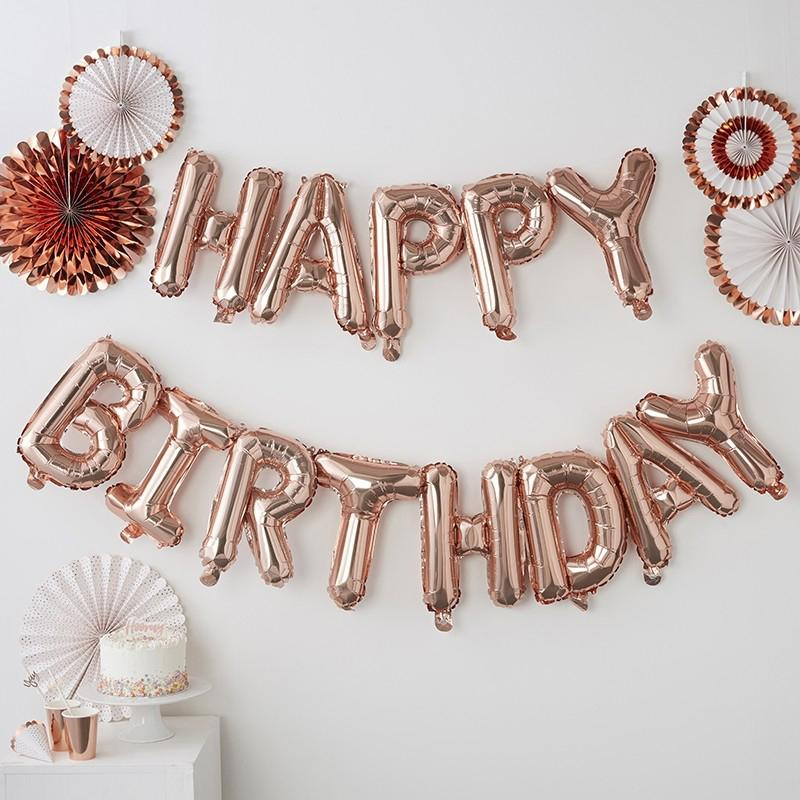 "A rose gold birthday balloon banner with a ""Happy Birthday"" message"