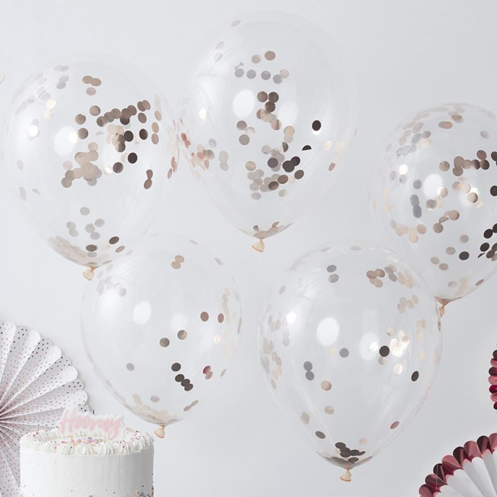 A bunch of clear latex party balloons filled with rose gold confetti pieces