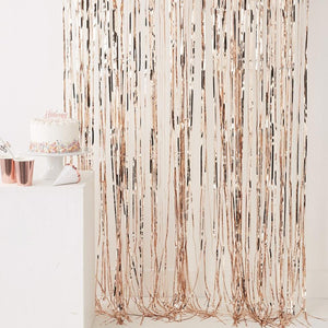 A rose gold foil fringe curtain hanging up at a party
