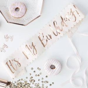 "A light pink birthday sash with a phrase written in rose gold foil saying ""It's My Birthday!"""