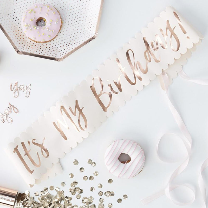 A light pink birthday sash with a phrase written in rose gold foil saying