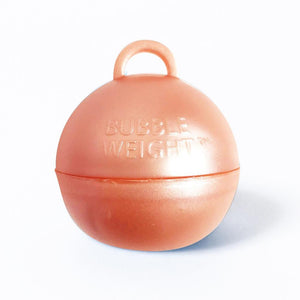 A round, rose gold-coloured balloon weight