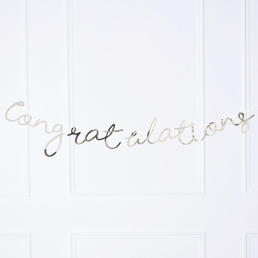 "A gold foiled party banner with a ""Congratulations"" message in cursive text"