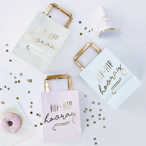 "3 pastel-coloured party bags with gold foil handles and a ""Hip Hip Hooray"" phrase"