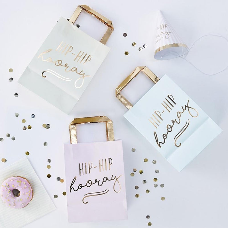 3 pastel-coloured party bags with gold foil handles and a