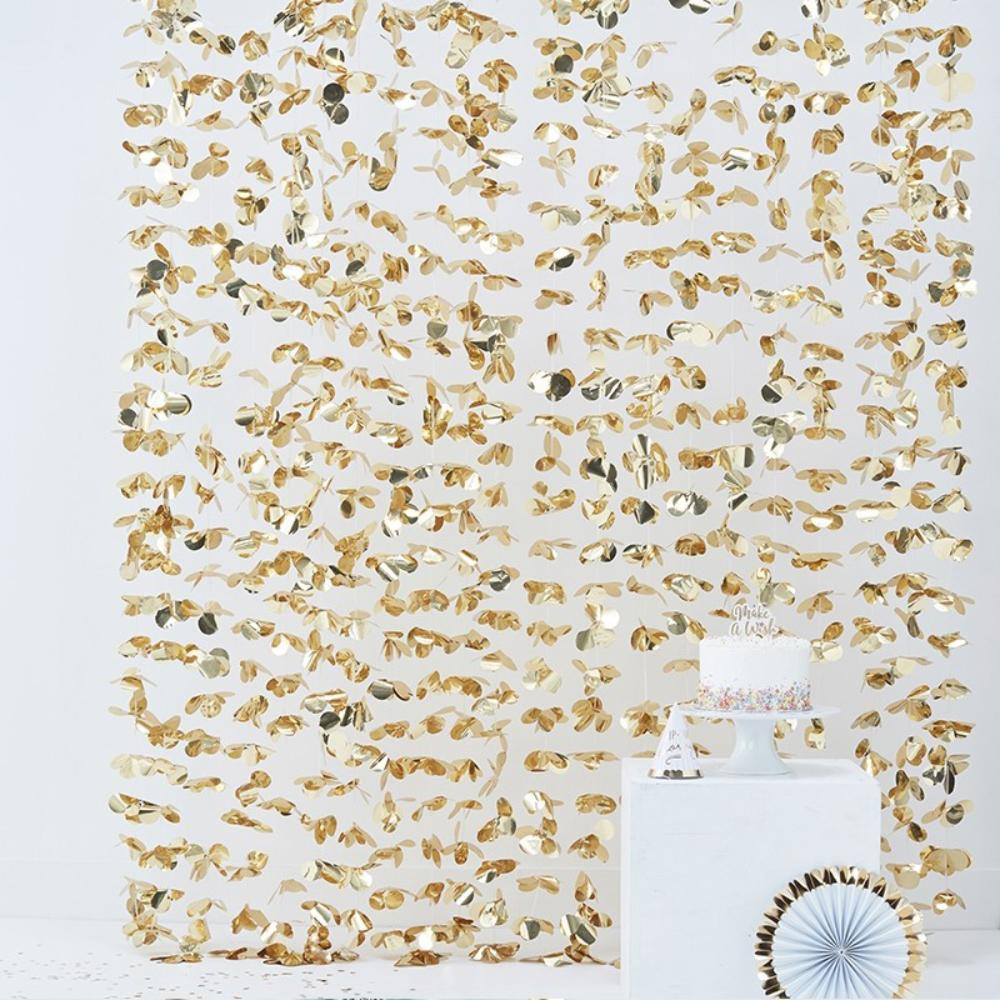 A gold foil petal backdrop for a party photobooth