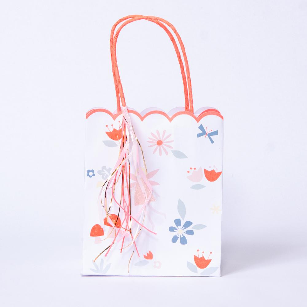 A fairy-themed party bag with a scalloped design and pastel pink handles