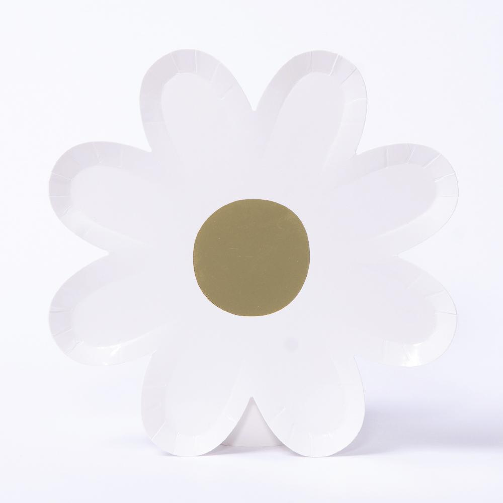 A white paper daisy-shaped party plate with a gold-foil centre