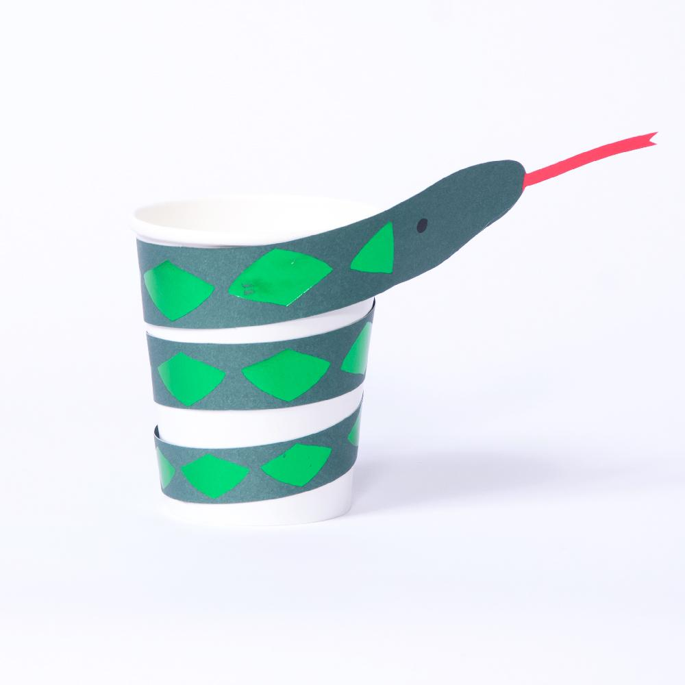 A jungle-party themed paper cup with a snake decoration wrapped around the outside