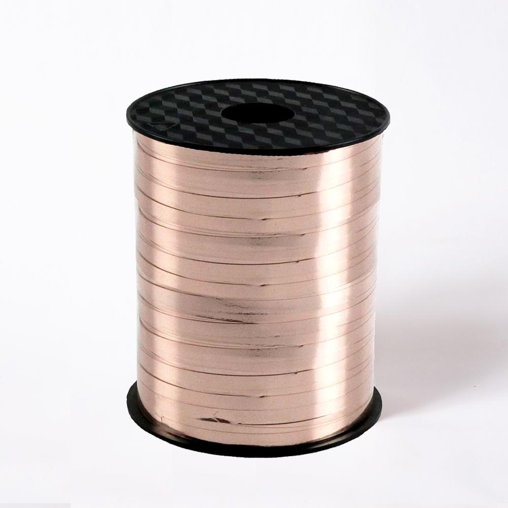 A reel of shiny rose gold party ribbon