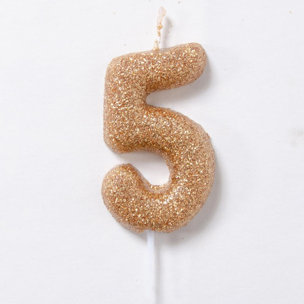 A glittery gold birthday candle in the shape of the number 5