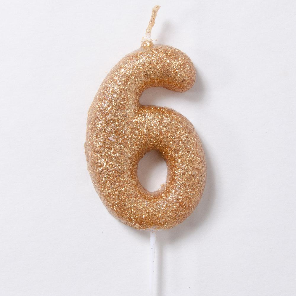 A glittery gold birthday candle in the shape of the number 6