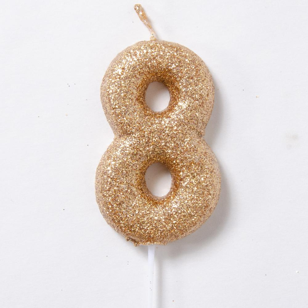 A glittery gold birthday candle in the shape of the number 8