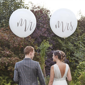 "A bride and groom carrying 2 large latex wedding balloons saying ""Mr"" and ""Mrs"""