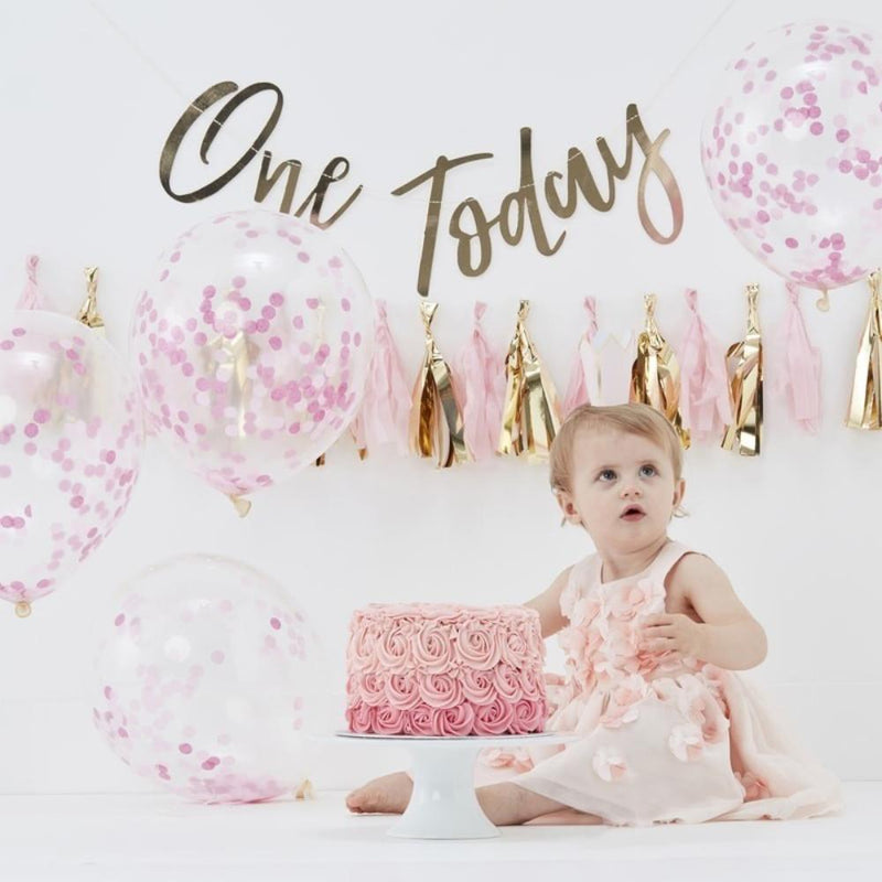 A small child surrounded by pink 1st birthday party decorations