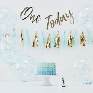 A blue and gold 1st birthday decorating kit set up on a party table