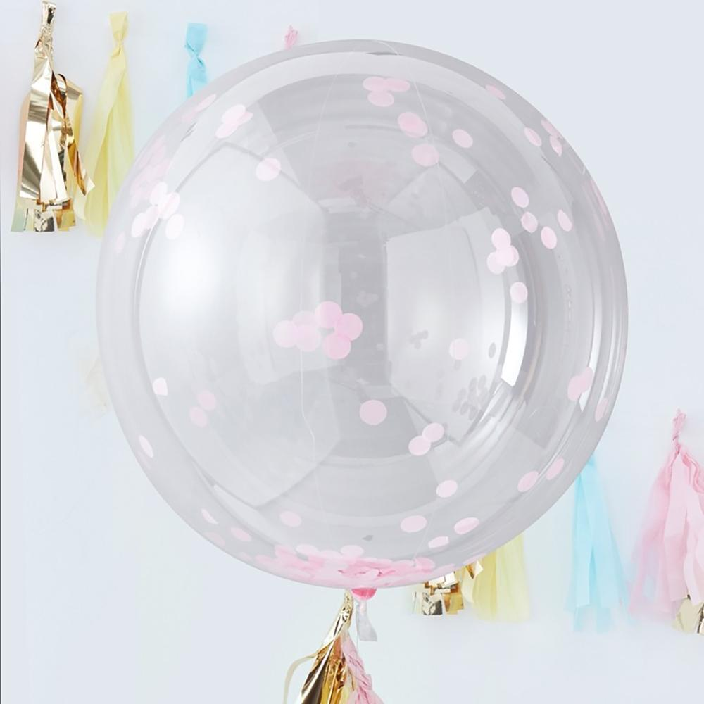 A clear spherical balloon filled with pastel pink confetti shapes