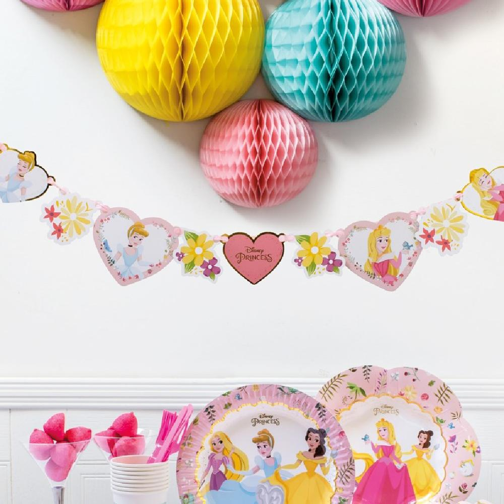 A Disney Princesses party scene featuring a party garland, honeycomb pom poms and party plates