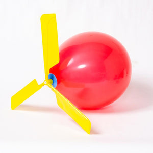 A red party balloon with a yellow balloon helicopter attached to the top
