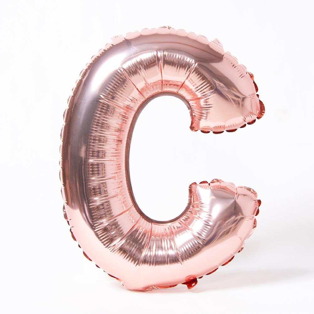 "A rose gold foil balloon in the shape of the letter ""C"""