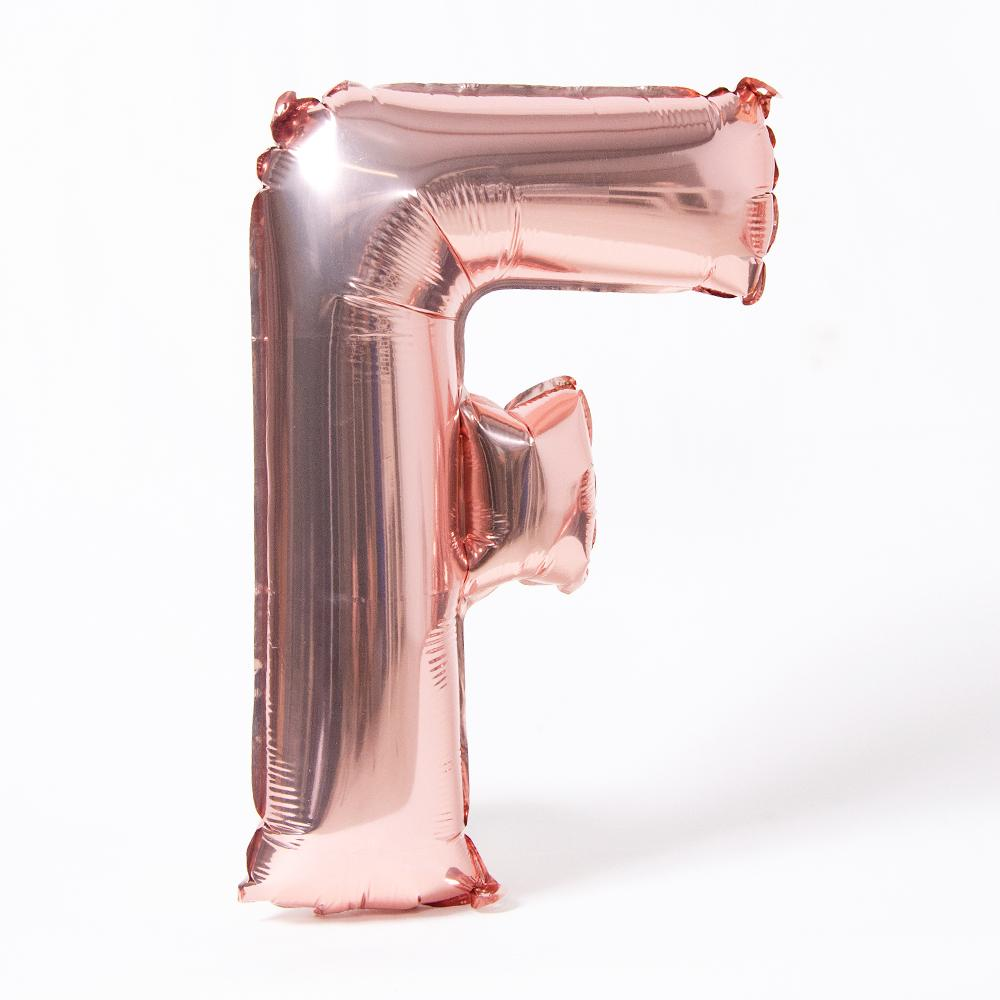 "A rose gold foil balloon in the shape of the letter ""F"""