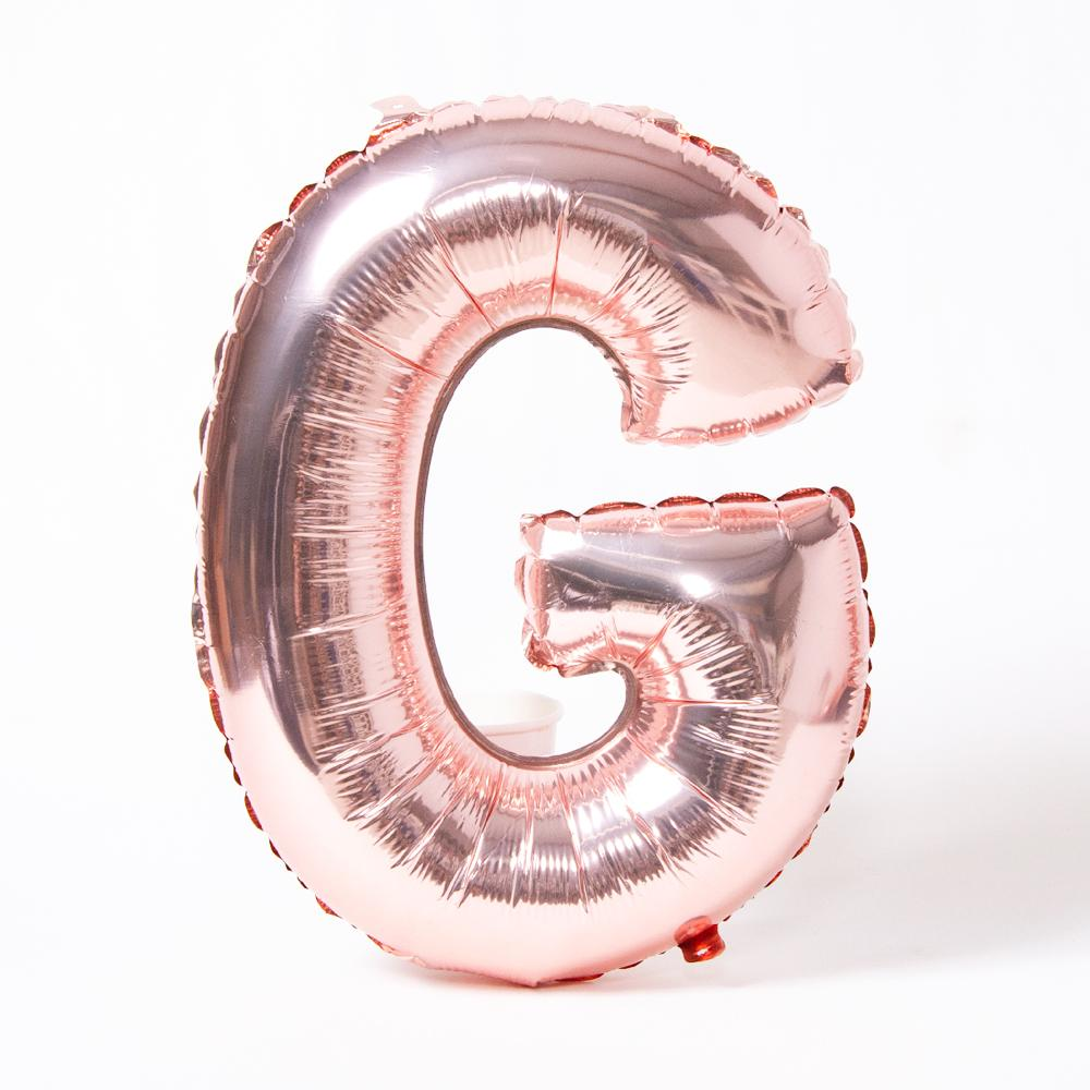 "A rose gold foil balloon in the shape of the letter ""G"""