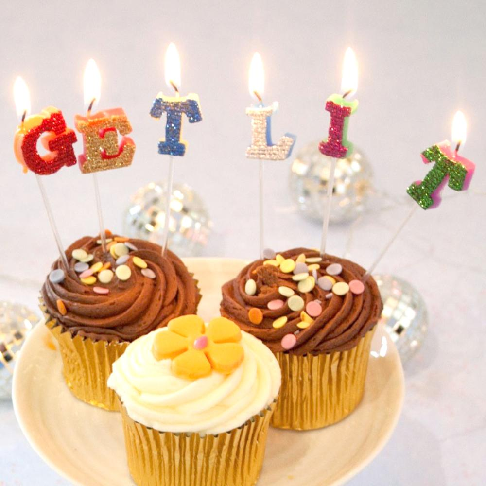 "3 party cupcakes with cake candles saying ""Get Lit"""