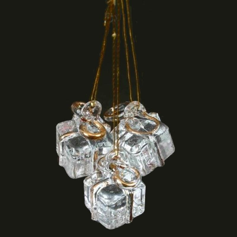 three clear presents wrapped in gold string to hang or tie on the Christmas tree