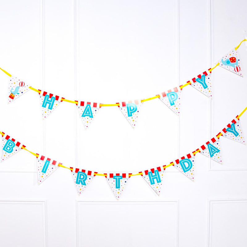 A circus-themed Happy Birthday party bunting with red and white stripes