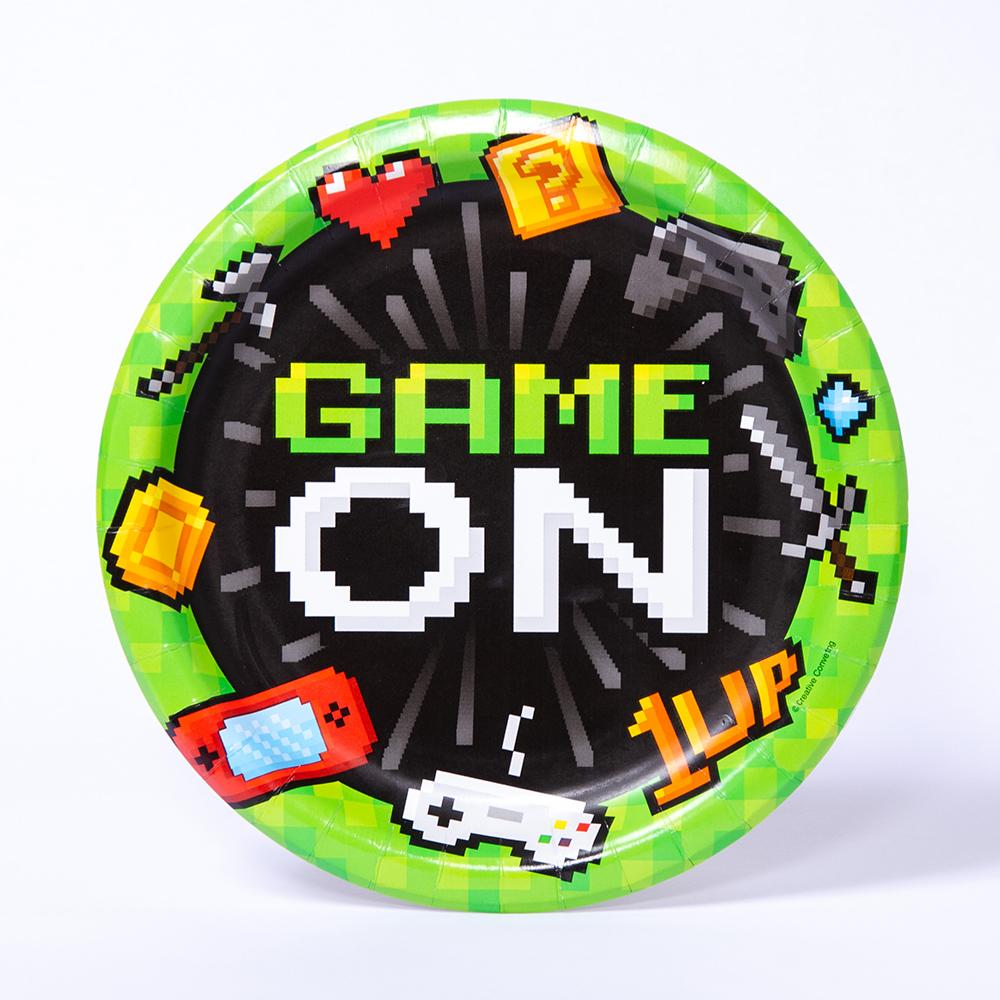 "A round gaming party plate with pixelated video game icons and a ""Game On"" phrase"