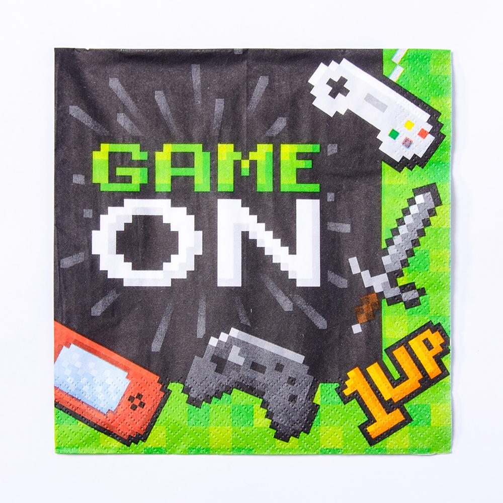 "A gaming party napkin with a pixelated phrase saying ""Game On"" and gaming icons"