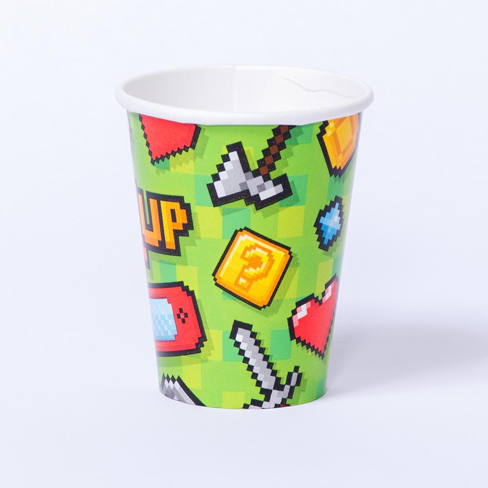 A paper party cup with a pixelated game icon design