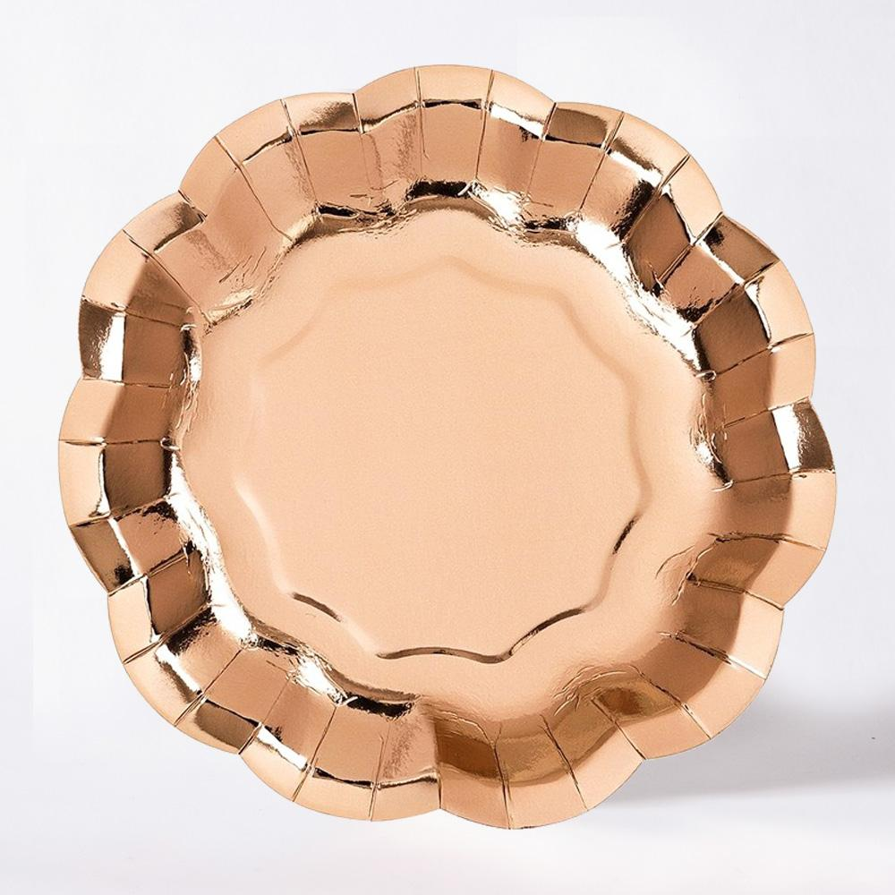 A shiny rose gold party plate with a scallop-edge design