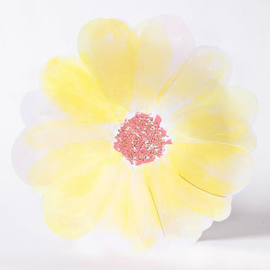 A yellow flower-shaped party plate with a glittery rose gold centre