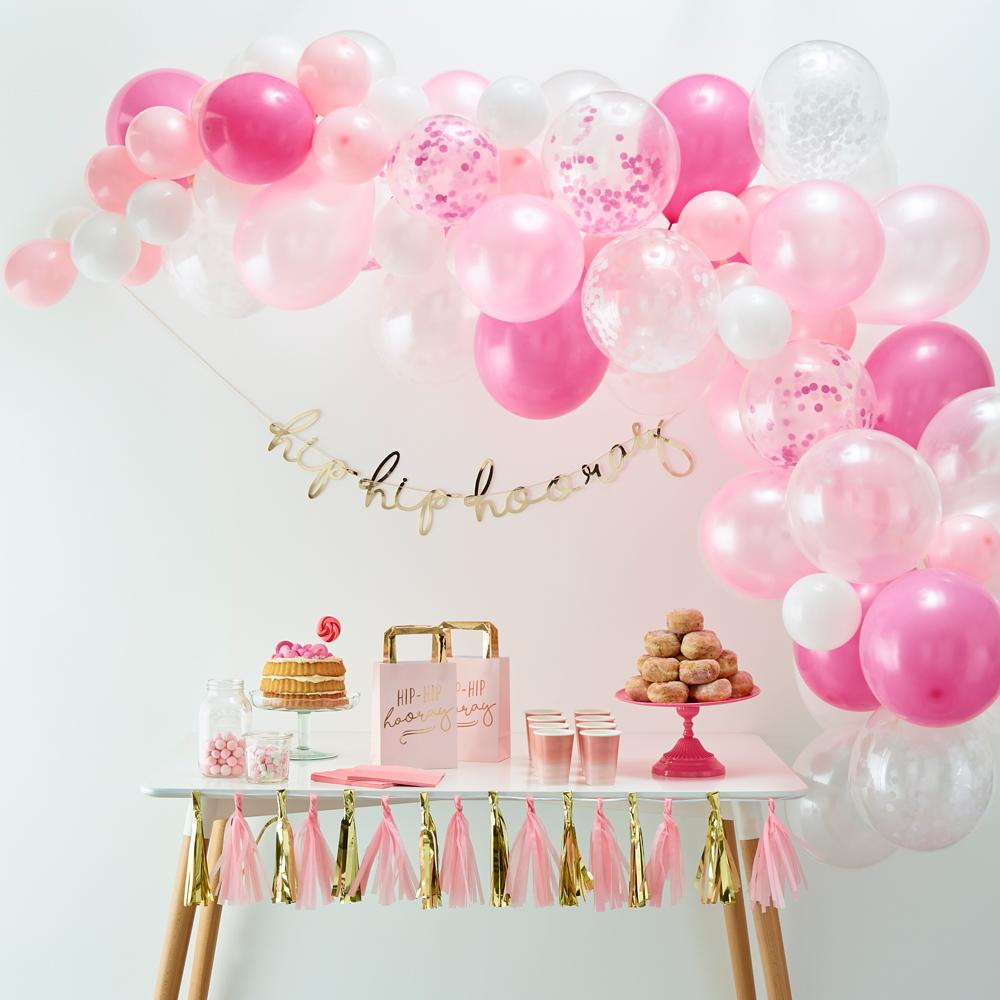 A pastel pink balloon arch placed above a party table centrepiece