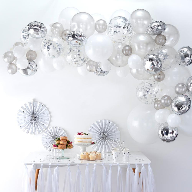 A silver-themed party balloon arch placed above a party table
