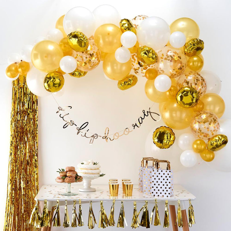 A party table with a large gold balloon arch hung up above it