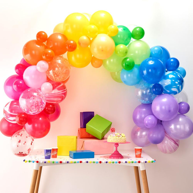 A balloon arch with rainbow colours placed above a party table