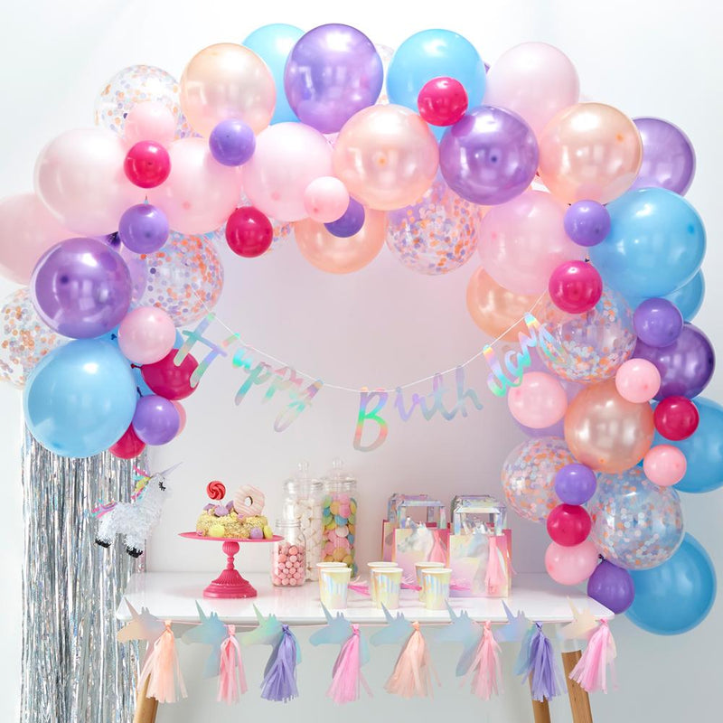 A large balloon arch with pastel-coloured balloons placed above a party table
