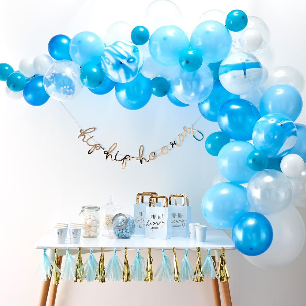 A blue balloon arch hung up above a party table