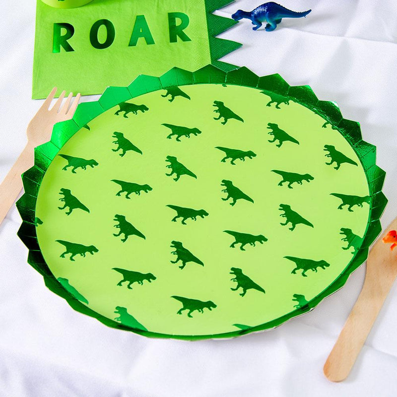 A round party plate featuring a green foil T-Rex pattern and a dino-spine rim